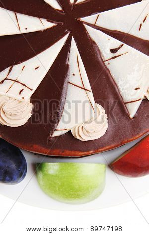 chocolate cream brownie cake topped with white chocolate slice and cream flowers decorated with fruits apple plum and grape on plate isolated over white background