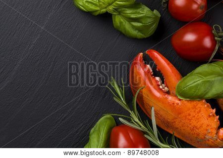 Lobster Leg On Blackbackground With Herbs And Tomatoes