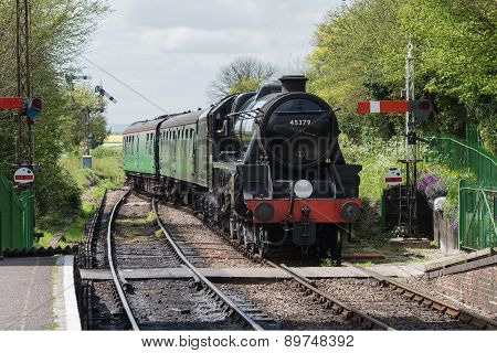 Steam train approaches Ropley station on the Watercress Line