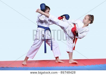 Paired exercises karate are performing sportsmens in karategi