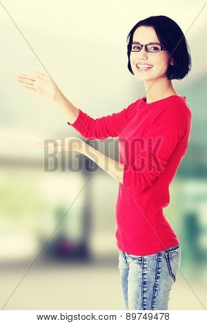 Happy , excited young woman presenting copy space on her palm.