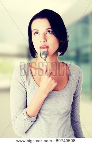 Beautiful woman with spoon in her mouth