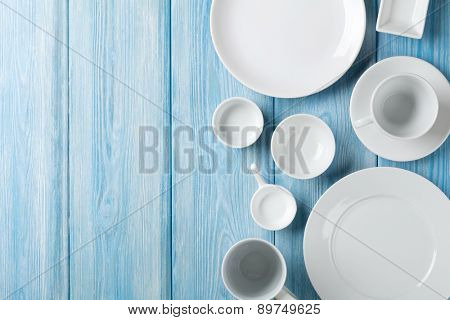 Empty plates and bowls on blue wooden background. Top view with copy space