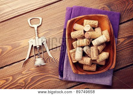 Wine corks and corkscrew over rustic wooden table background. Top view
