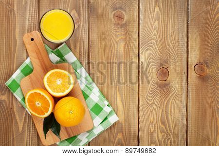 Oranges and glass of juice. View from above over wood table background with copy space