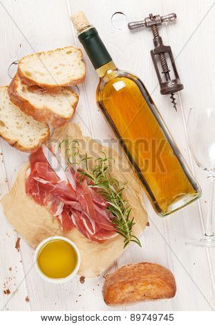Prosciutto, wine, ciabatta, parmesan and olive oil on wooden table. Top view