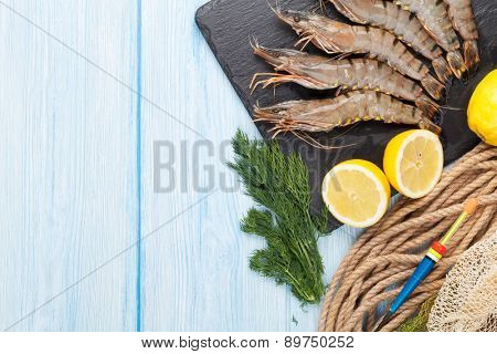 Fresh raw tiger prawns and fishing equipment on wooden table. Top view with copy space