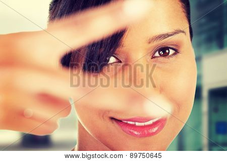 Happy woman gesturing peace sign