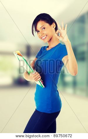 Happy young woman holding documents
