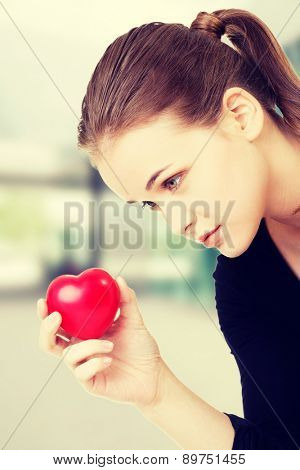 Thoughtful woman holding heart model