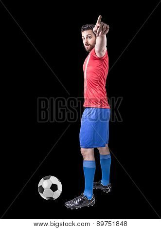 Soccer player on red and blue uniform on black background