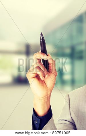 Businessman holding a marker pointing high