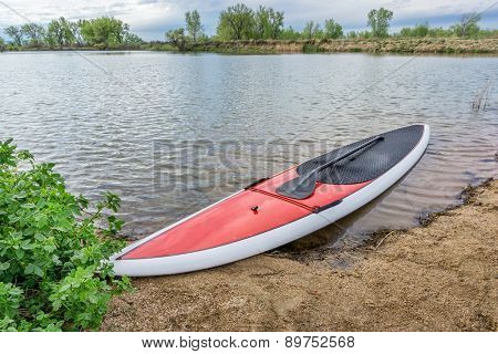red stand up paddleboard on a lake shore in Colorado,. early spring