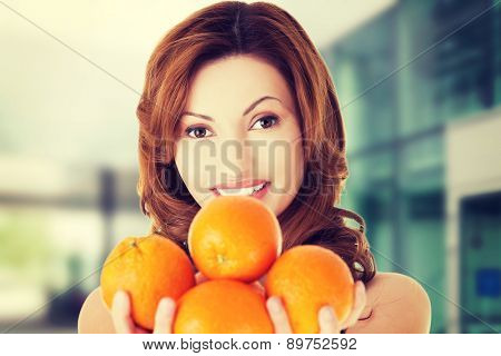 Happy woman holding group of oranges