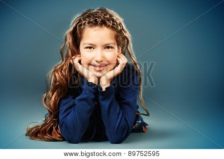 Portrait of a pretty teen girl with beautiful long hair smiling at camera. Studio shot.