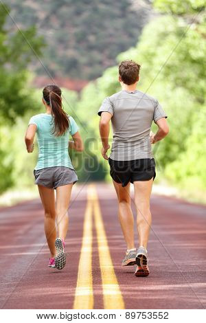 Runners running and jogging for health and fitness. People on fitness run on road in nature. Couple, woman and man training outside for fitness and healthy life. Full body length rear view of back.