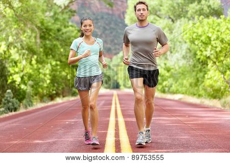 Running Health and fitness. Runners on run training during fitness workout outside on road. People jogging together living healthy active lifestyle outside in summer. Full body length of woman and man