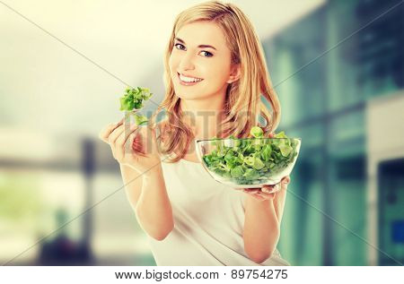 Smiling woman eating healthy salad