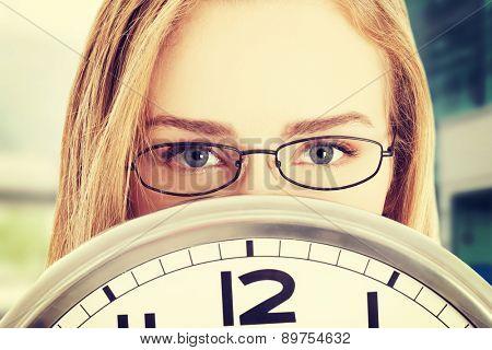 Caucasian business woman holding clock
