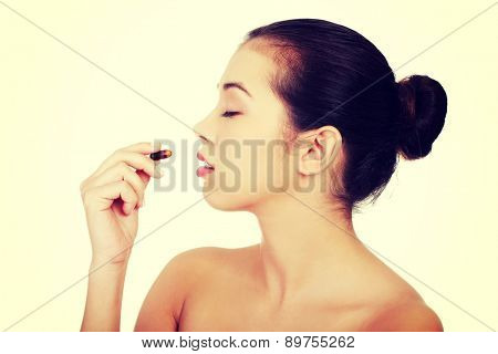 Young beautiful woman taking pill