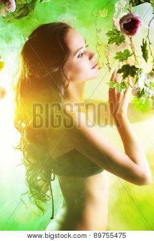 Beautiful brunette woman in bikini among tropical plants. Beauty, fashion. Spa, healthcare. Tropical vacation.