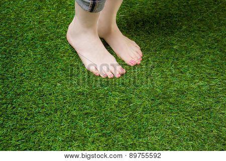 Woman legs standing  on green grass
