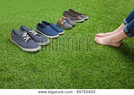 Shoes standing  on grass in front of bare legs