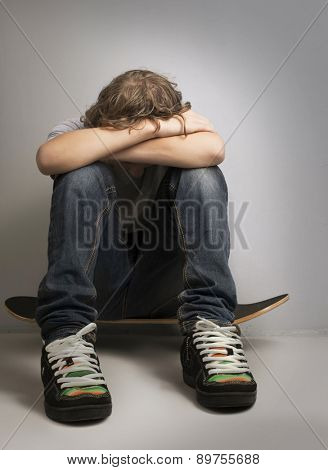 sad teenager sitting on skateboard