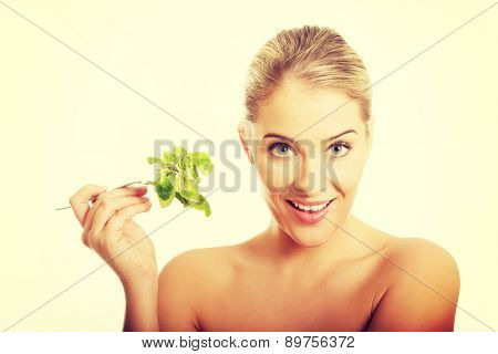 Happy smiling nude woman holding a fork with lettuce.