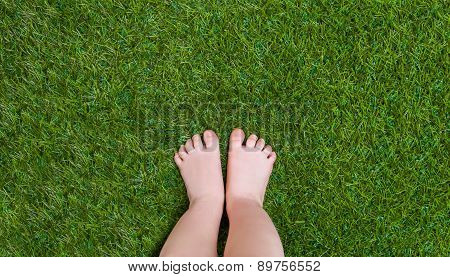 Baby legs standing  on green grass