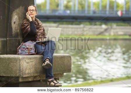 Young woman with laptop talking on the phone, outdoors in the city.