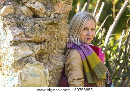 Young fashionable blonde woman near a stone wall in a city Park.