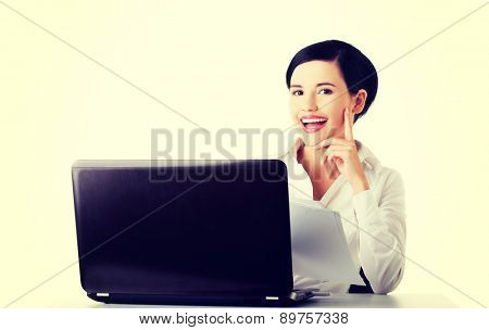 Happy beautiful businesswoman using laptop