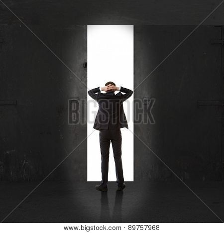 Infinity. Rear view of a businessman standing in front of the exit light