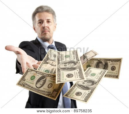 Handsome adult businessman throwing dollar