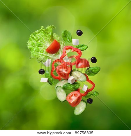 flying salad on natual green backround - red tomatoes, pepper, cheese, basil, cucumber and olives