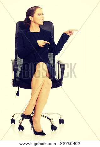 Young businesswoman sitting on chair and pointing on copy space