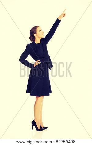Pretty young businesswoman pointing up
