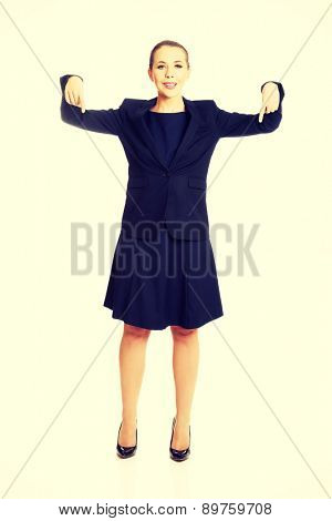 Pretty happy businesswoman pointing down