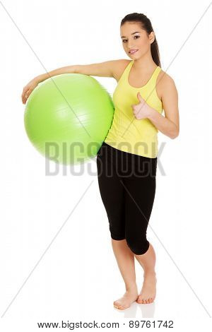 Young fitness woman with pilates ball and thumbs up.