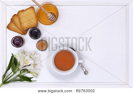 breakfast table with tea, cup of tea, flower,  jam, bread and honey