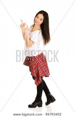 Young student rock woman pointing up.