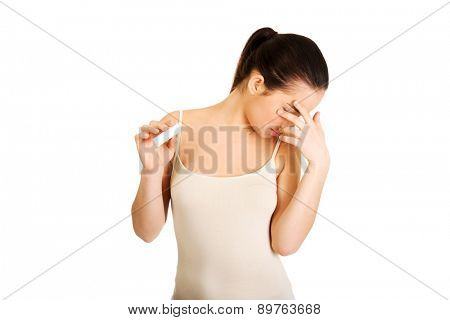 Unhappy sad woman with pregnancy test.