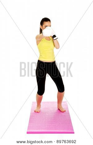 Attractive fitness woman wearing boxing gloves.