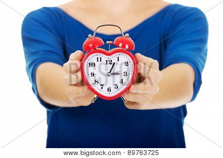 Young happy woman holding alarmclock.