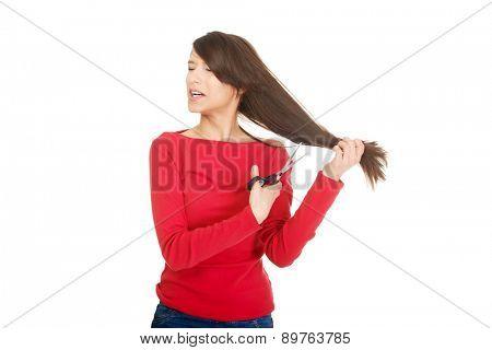 Young despair woman cutting her hair.