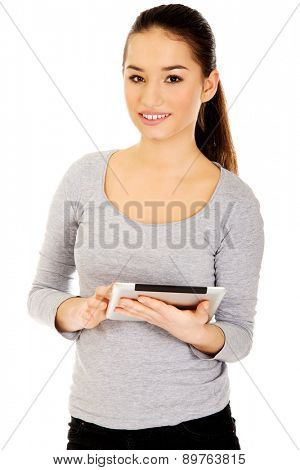 Casual teenage woman with tablet.