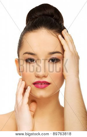 Beautiful woman with full make up touching head.