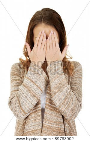 Beautiful woman covering face with her hands.