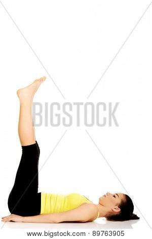 Fitness woman with her legs up practising yoga.
